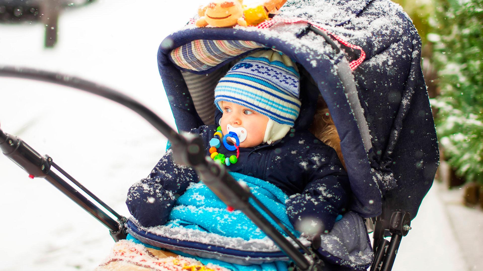 75aff28e Bilde av liten gutt i barnevogn med masse klær.