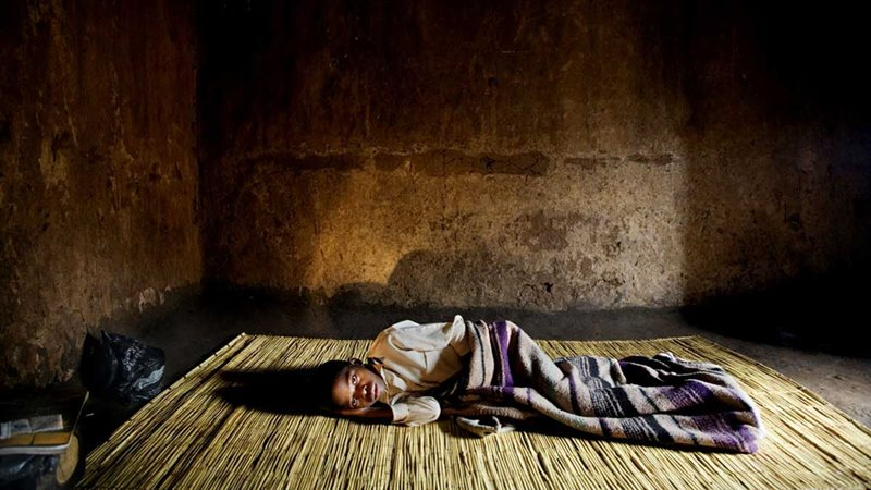 Photo of a person lying in a house on a straw mat covered by a blanket.